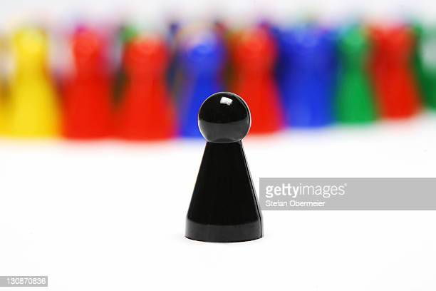 group of chinese checkers figures with single black token - one animal stock photos and pictures