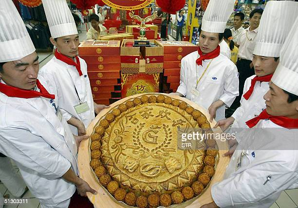 A group of Chinese chefs show off their creation a giant mooncake for the upcoming midautumn festival in Beijing 14 September 2004 The giant mooncake...
