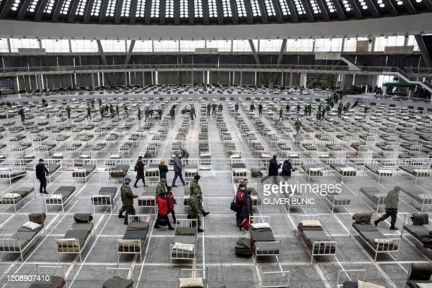 TOPSHOT A group of Chinese doctors inspect a makeshift hospital inside a hall at the Belgrade Fair to accommodate people suffering from mild symptoms...