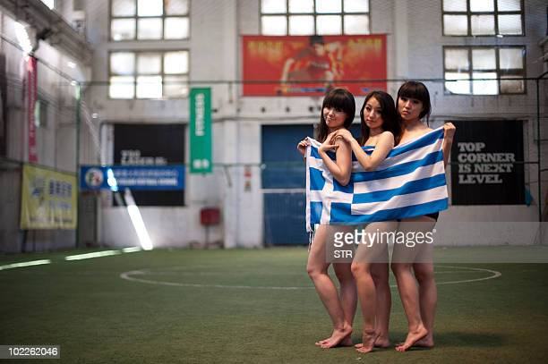 A group of Chinese girls pose with a Greek flag as part of a World Cup cheerleaders contest organised to attract more football fans to watch the...