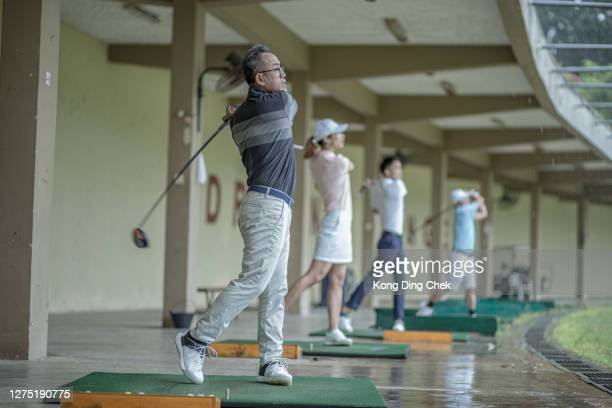 a group of chinese golfers teeing off and swing driver at golf driving range during rainy day. - individual event stock pictures, royalty-free photos & images