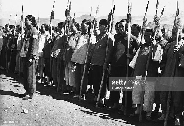 Group of Chinese male and female guerrillas on parade with their spears.