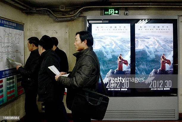 A group of Chinese men check the map in front of a poster for the Hollywood disaster movie '2012' at a subway station in Beijing on December 20 2012...