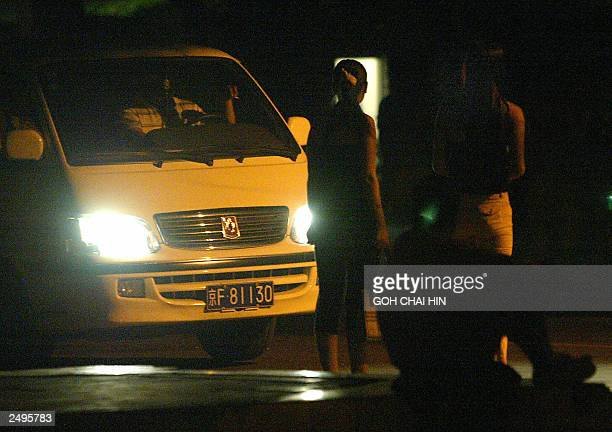 A group of Chinese prostitutes wait along a sidewalk of a dimlylit street in the eastern ringroad of the capital city Beijing 10 August 2003 under...