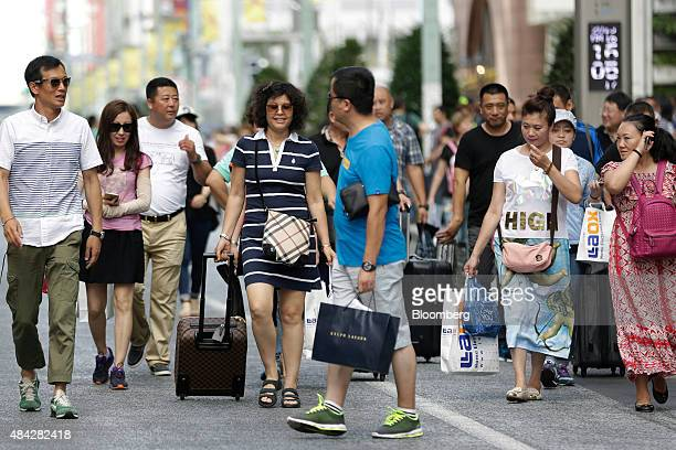 A group of Chinese tourists carry shopping bags and suitcases in the Ginza district of Tokyo Japan on Sunday Aug 16 2015 Japan's economy contracted...