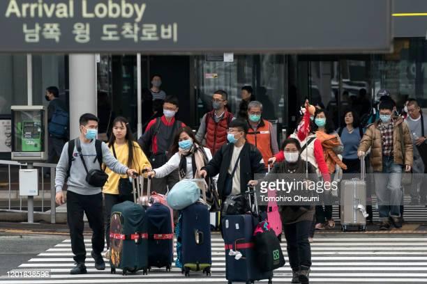 Group of Chinese tourists walks outside the arrival lobby at Narita airport on January 24, 2020 in Narita, Japan. While Japan is one of the most...