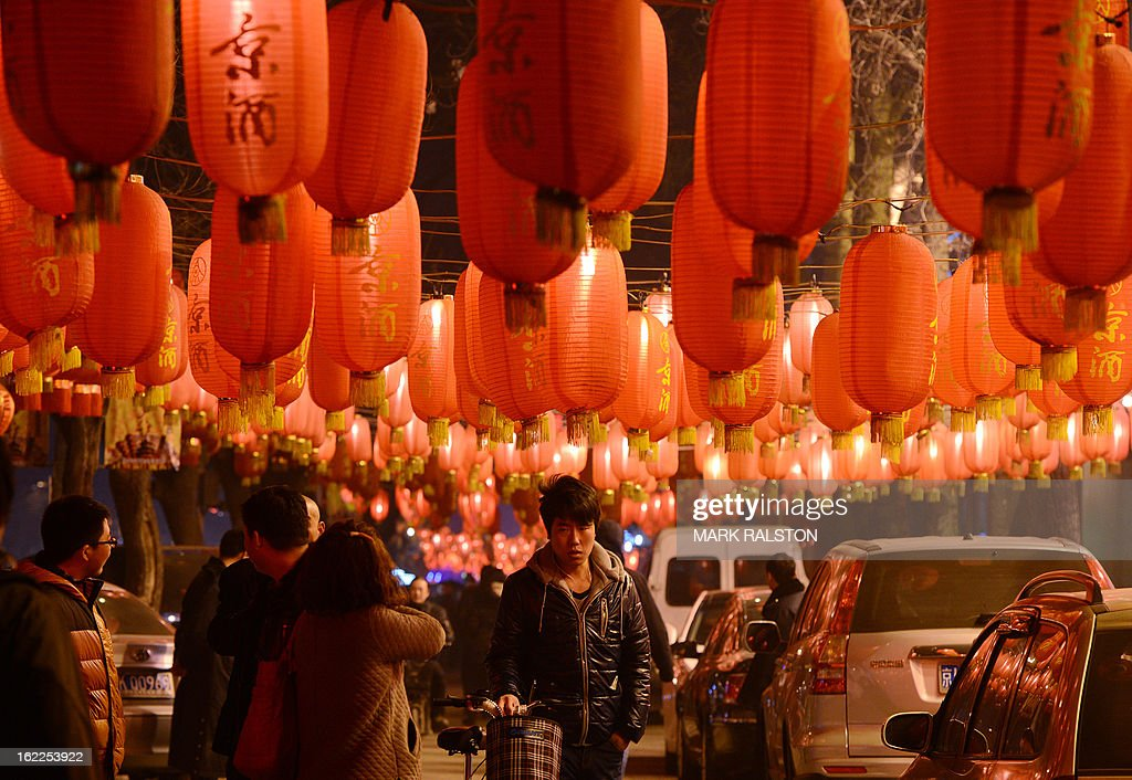 A group of Chinese walk beneath lanterns as the city prepares for the traditional Lantern Festival which falls on the 15th day of the Lunar New Year and officially ends the celebrations, in Beijing on February 21, 2013. The festival which dates back more than 2000 years to the Han Dynasty sees China's cities becoming a sea of lanterns and fireworks. AFP PHOTO/Mark RALSTON