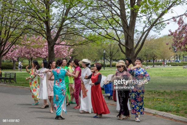 group of chinese women in traditonal dresses practicing dance - flushing queens stock pictures, royalty-free photos & images