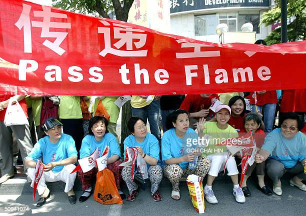 A group of Chinese women rest beneath a banner as they wait to welcome the Olympic flame passing by in Beijing 09 June 2004 during the Beijing leg of...