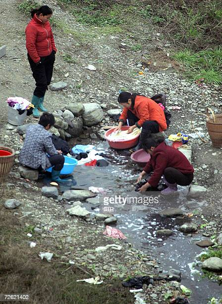 A group of Chinese women wash their laundry in a stream near their village in Zhangjiajie central China's Hunan province 21 November 2006 The amount...