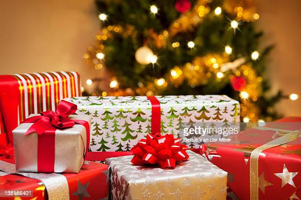 group of christmas gifts in front of tree. - christmas present stock pictures, royalty-free photos & images