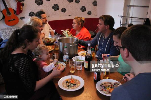 A group of citizens sitting around a table debating the development of the city while eating soup in a private apartment in Stuttgart Germany 15 June...