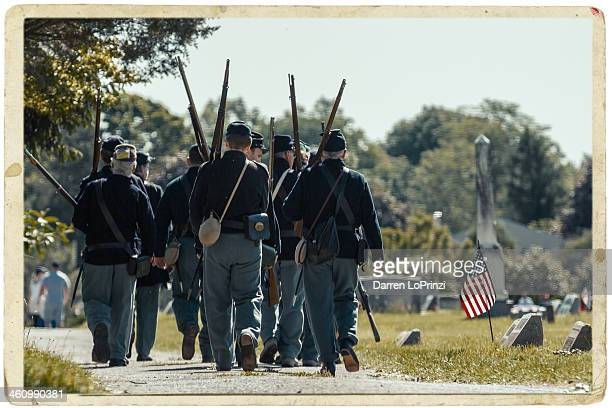 CONTENT] A group of Civil War Reenactors who had just marched in the Memorial Day Parade take a break and walk through a cemetery to honor the many...