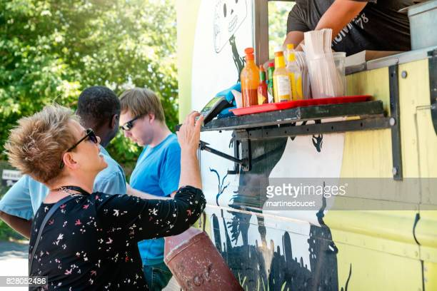 Group of clients around a food truck in a park.
