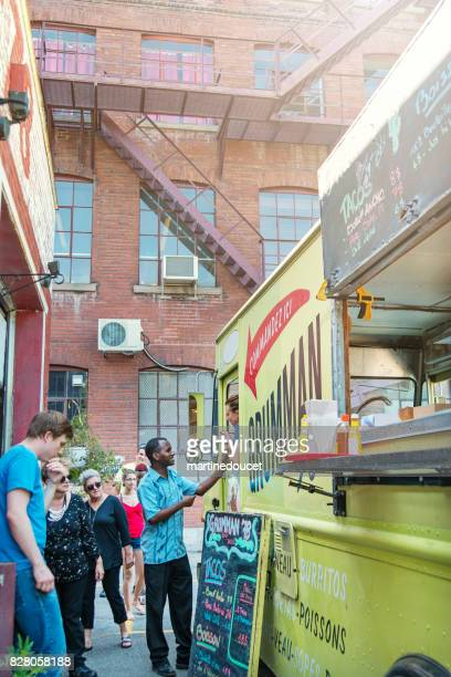 Group of clients around a food truck in city street.