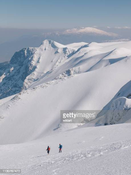 group of climbers are walking in the mountain peak - snowcapped mountain stock pictures, royalty-free photos & images