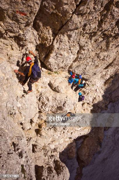 Group of climbers ascending the Santner Pass Via Ferrata, in the Dolomites mountains . Via Ferratas are climbing routes permanently equipped with a...
