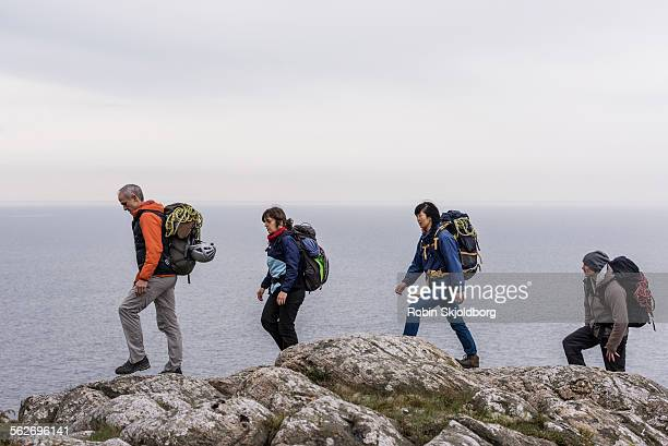 group of climbers hiking on cliff - robin skjoldborg stock pictures, royalty-free photos & images