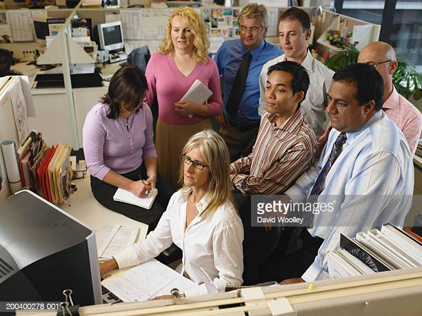 Group of colleagues around mature woman at desk, elevated view