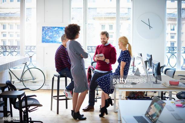 group of colleagues having an informal meeting - creative occupation stock pictures, royalty-free photos & images