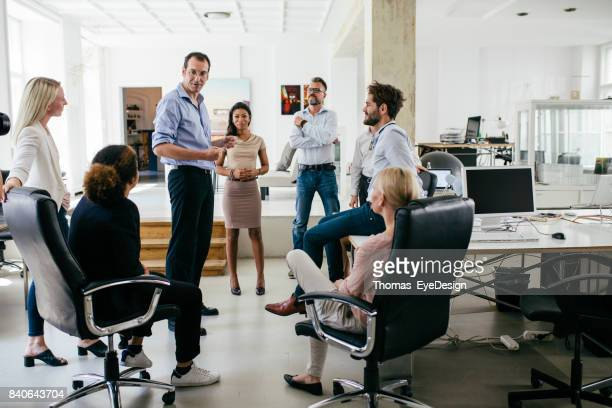 group of colleagues holding meeting in modern office space - colletti bianchi foto e immagini stock