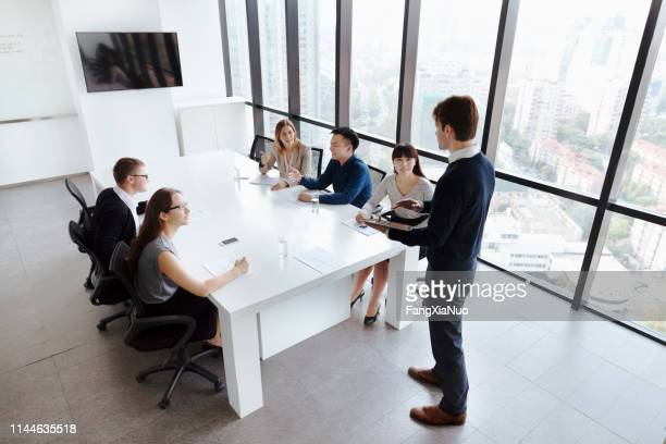 group of colleagues in office meeting together - visual china group stock pictures, royalty-free photos & images
