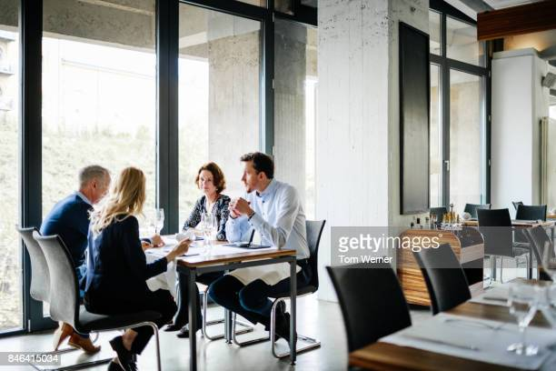 group of colleagues sitting by window in restaurant for business lunch. - collègue photos et images de collection
