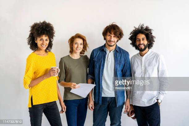 group of colleagues standing in front of white background - small group of people stock pictures, royalty-free photos & images