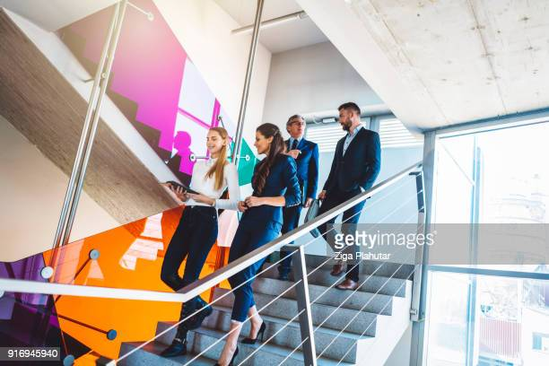 A group of colleagues walking down the stairs