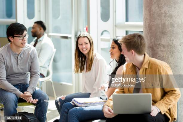 group of college friends study and talk in school lobby - community college stock pictures, royalty-free photos & images