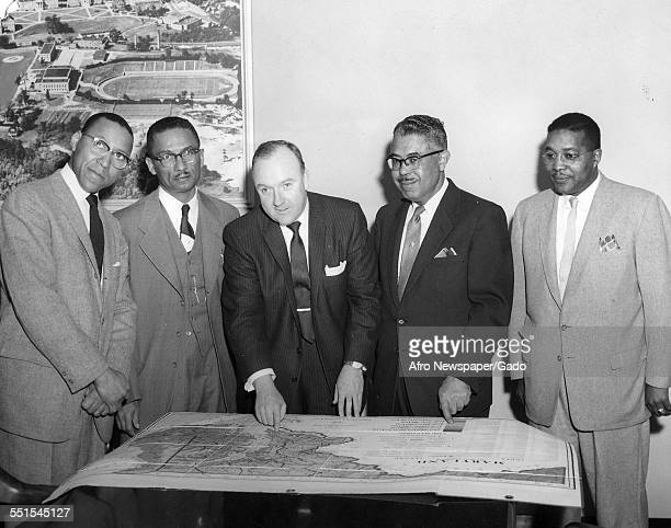 A group of college officials gathering at a meeting looking over a map or ground plans for expansion Baltimore Maryland 1958
