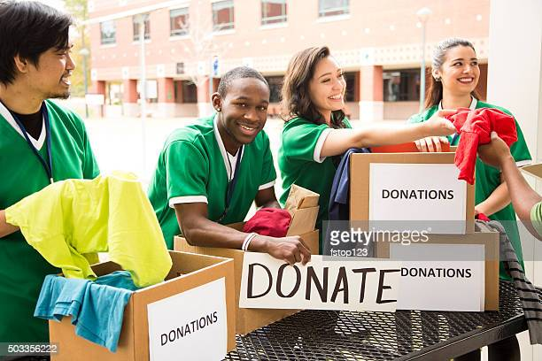 Group of college student volunteers collect clothing donations. Charity.