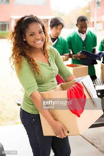 Grupo de estudiantes universitarios voluntarios recolectar ropa donaciones. Caridad.