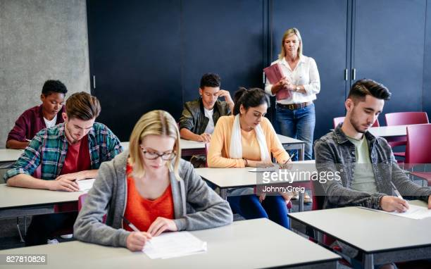 Group of college students in exam, teacher watching