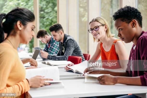 group of college students sitting at table, reading and smiling - 20 29 years stock pictures, royalty-free photos & images