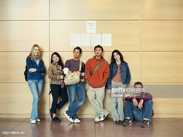 Group of college students standing against wall,   grades posted above