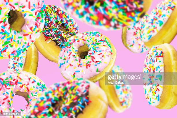 Group of colorful donuts levitating in pink background.