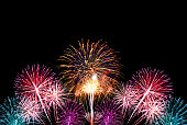 Group of colorful fireworks on dark background.