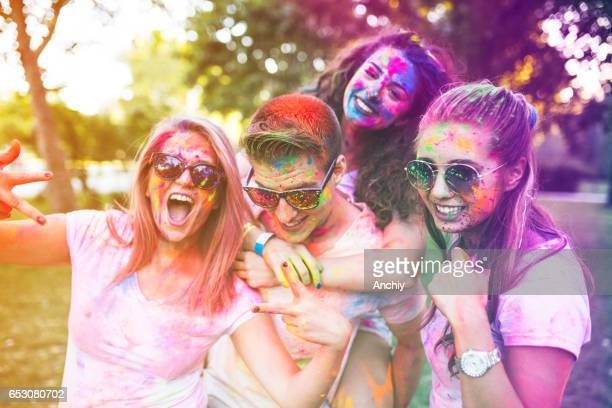 Group of colorful friends playing with color dust at the countryside