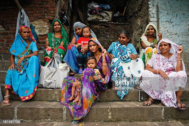 Group of colourfully dressed local women sit together on the steps of the ancient Banganga Tank, located in the Walkeshwar Temple Complex in Malabar...