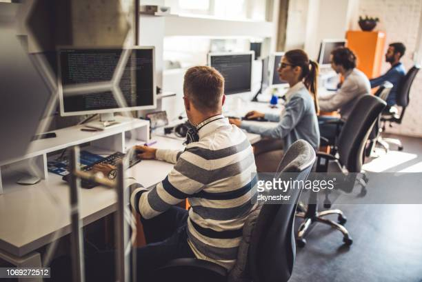 group of computer programmers working on pc's in the office. - technology stock pictures, royalty-free photos & images