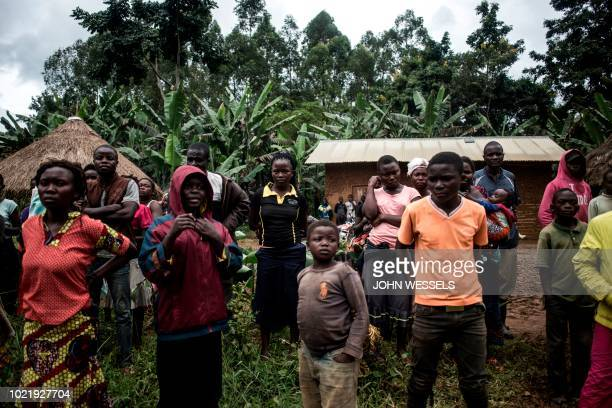 A group of Congolese look at a corpse of a suspected Ebola case being picked up on the side of the road linking Beni to Mangina on August 23 2018 in...