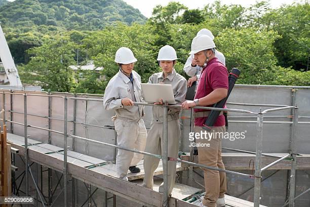 のグループ建設作業員を見ている、ノートパソコン