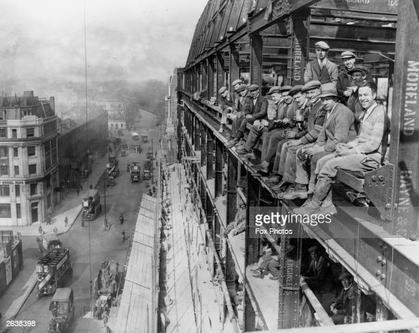 Group of construction workers sitting on the framework of the building they are working on during their lunch break, high above a London street.