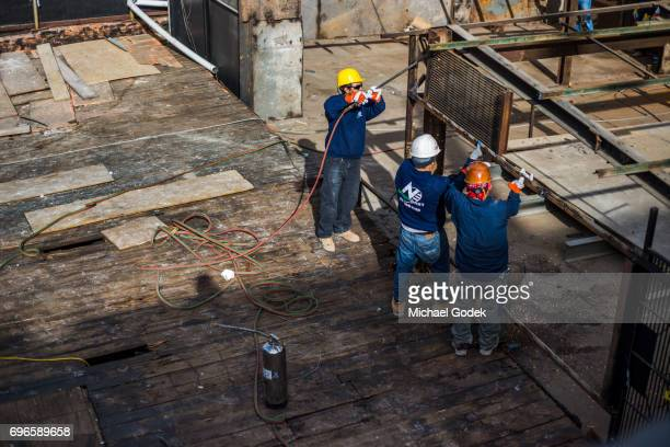A group of construction workers work with a torch to cut through a steel frame during demolition of a building