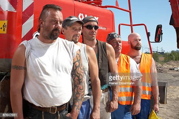 Grupo de trabalhadores de construção em frente da máquina