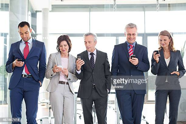 Group of corporate professionals using mobile phone