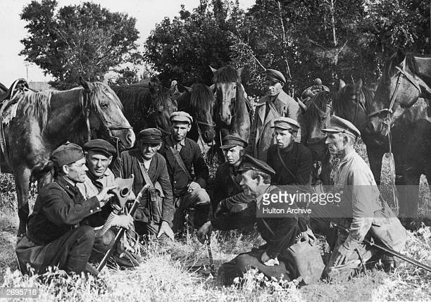 A group of Cossack fighters crouch in a field while a soldier demonstrates the use of a gas mask during the Russian Civil War that followed the...