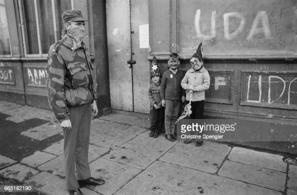 A group of costumed children stand near a masked soldier in Belfast Belfast residents suffer from continuous street battles in the ongoing conflict...