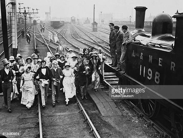 A group of costumed men and women march along a track to a waiting passenger train during celebrations marking the constuction of the world's first...